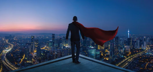 A super hero stands on top of a building overlooking a city.