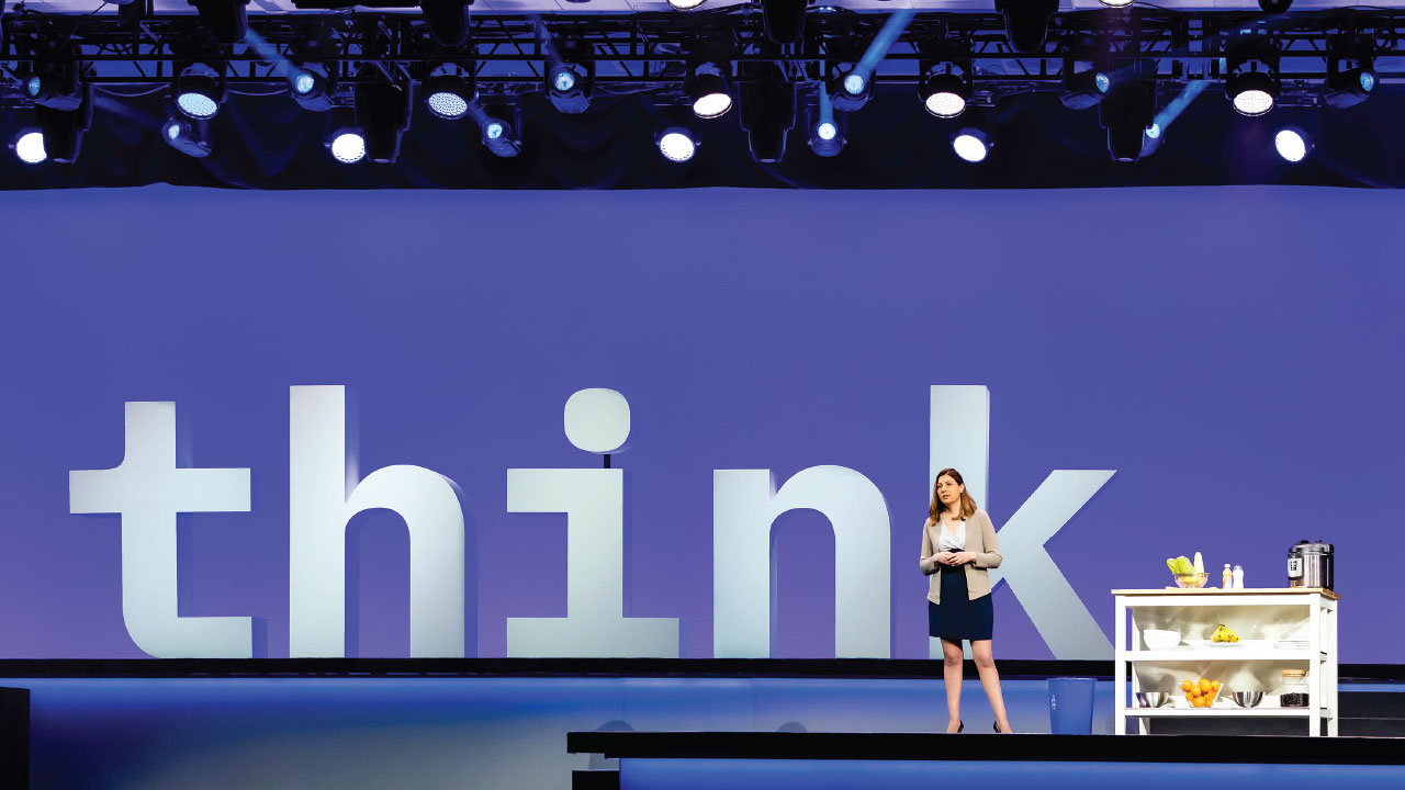 Photograph of a woman speaking onstage at Think 2019.