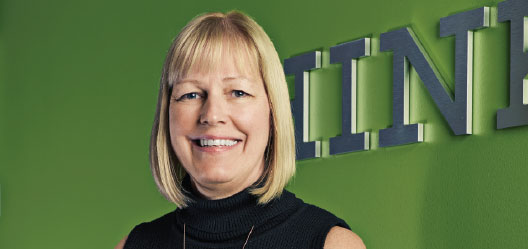 A photo of a woman with a blonde bob and bangs stands in front of a green wall.