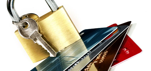 A padlock and key are straddling a handful of credit cards