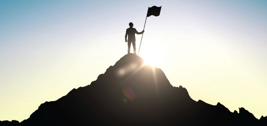 A figure stands on top of a mountain with a flag.