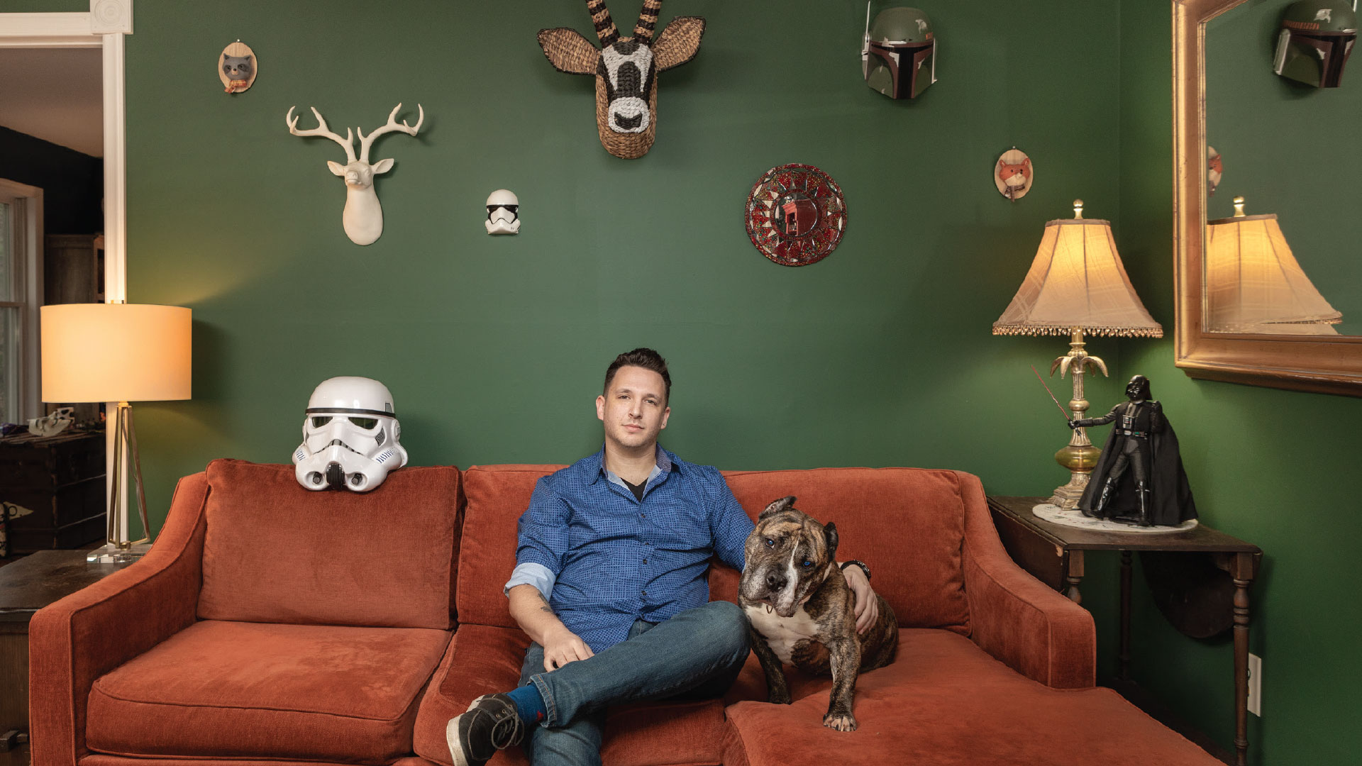 Tony Turetsky is photographed on a red couch against a green wall with his dog.