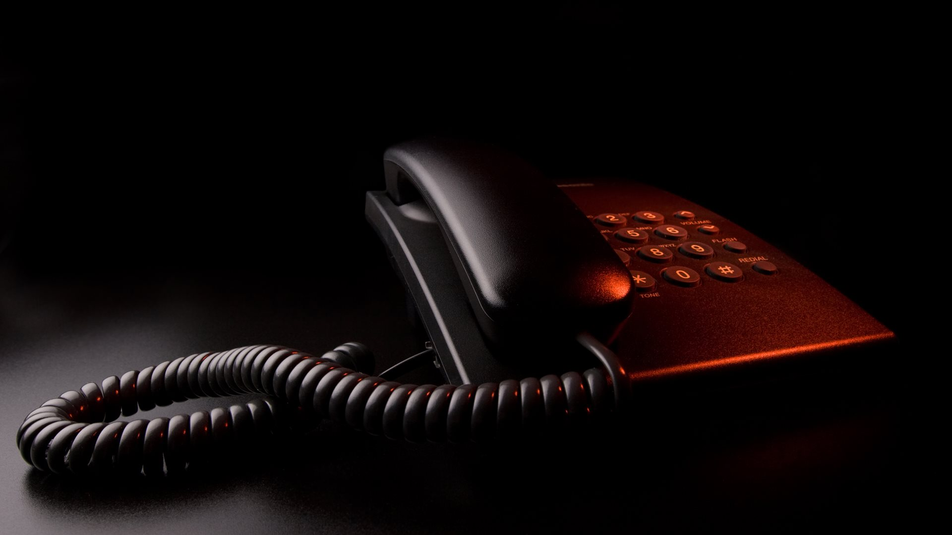 Black old fashioned phone with red light shining on it.