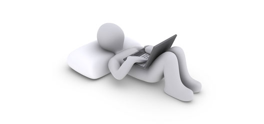 Gray humanlike-figure laying on a pillow using a laptop.