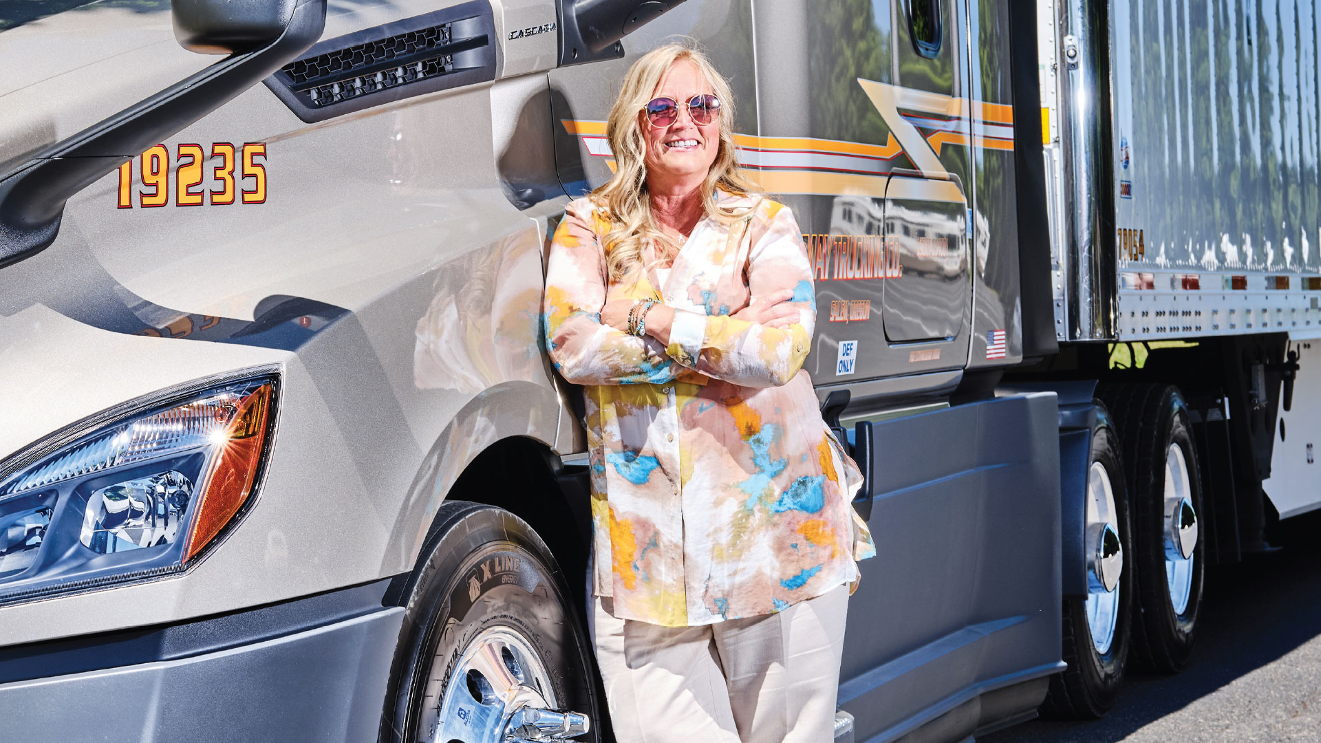 Becki Wagoner poses in front of a silver semi truck