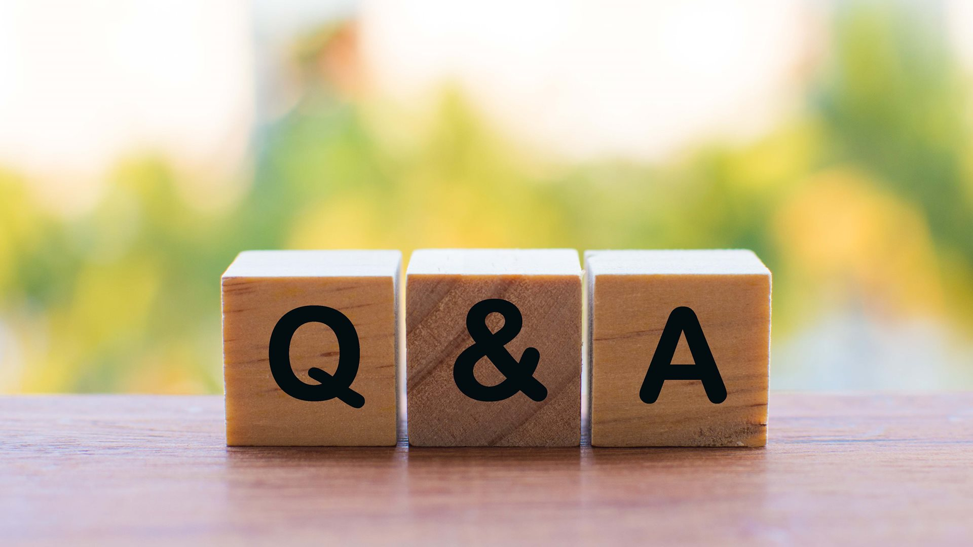 """Q&A"" blocks on a table against a green blurred photo background"