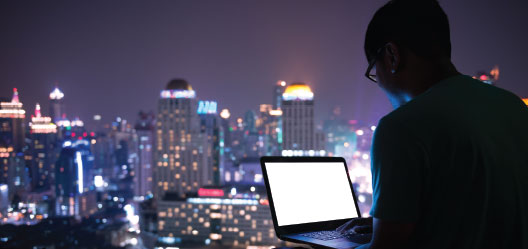 On the righthand side of the picture, a man sits with his back to the camera facing a laptop in his lap. The background a city skyline during a purple-colored sunset.
